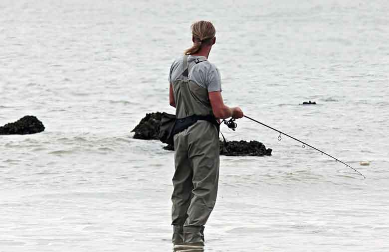 un pêcheur en bord de mer bien équipé